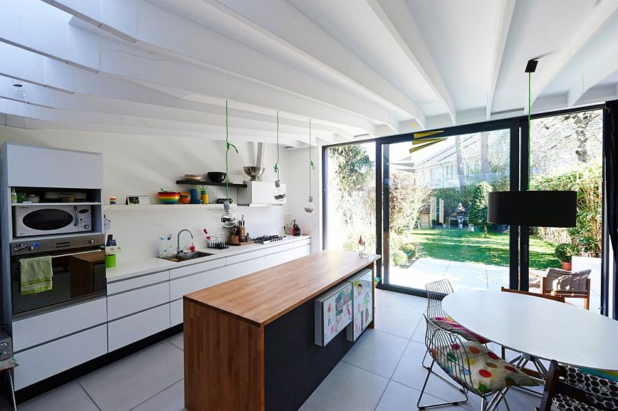 Small kitchen and dining area connected with the simple backyard using framed glass doors
