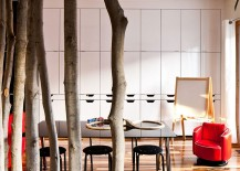 Use of tree trunks to create a natural, whimsical partition in the dining area