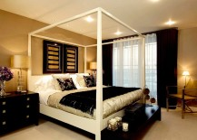 Wallpapered walls in gold and black decor and throws give the master bedroom a luxurious look