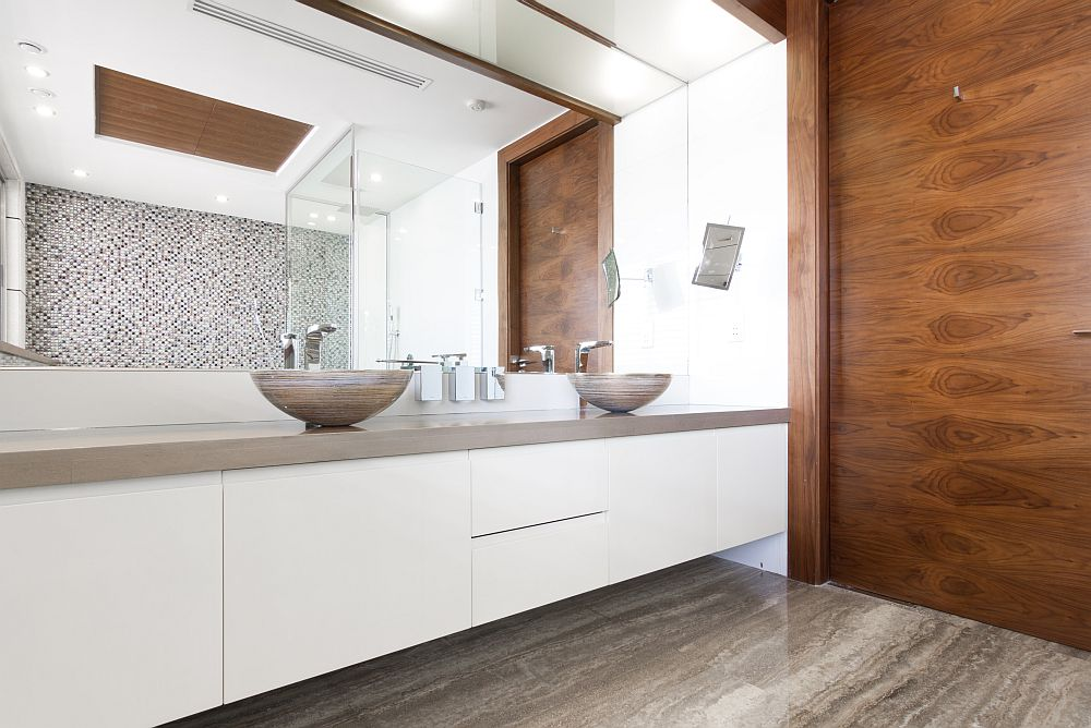 Wooden accent wall and vanity in white with twin sinks inside the bathroom