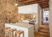 Wooden-ceiling-beams-and-stone-wall-stand-in-contrast-to-the-sleek-white-kitchen-217x155