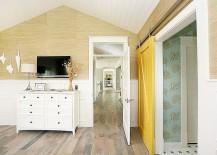 Yellow barn door adds color to the eclectic bedroom