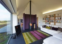 Bright purple accent wall separates the living area from the kitchen and dining spaces