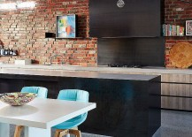 Contemporary kitche with a charming brick wall, sleek black island and dining area