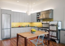 Contemporary kitchen with gray cabinets and yellow backsplash and a skylight