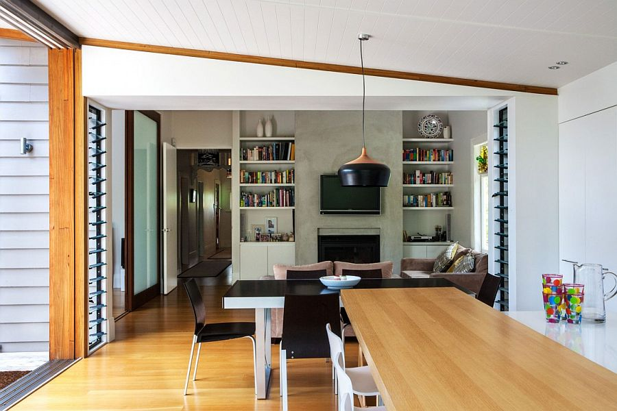 Dining and sitting area with large bookshelf and concrete walls
