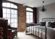 Elegant bedroom with brick wall and wrought iron bed frame