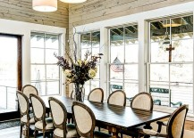 Farmhouse style dining room with high ceiling and glass windows