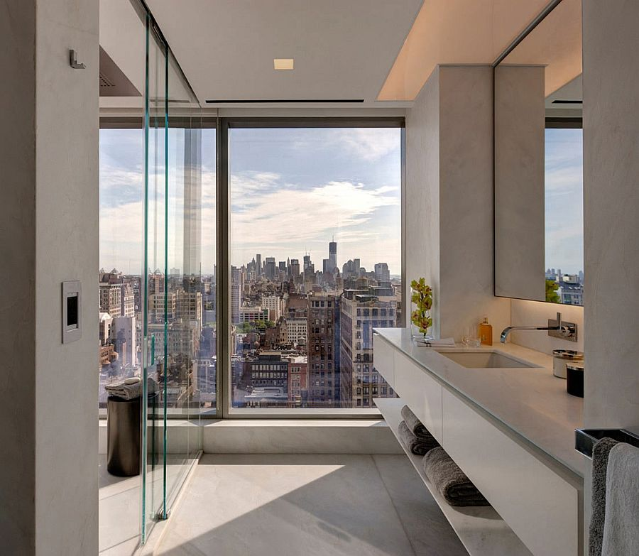 Glass walls separate the bedroom from the bathroom
