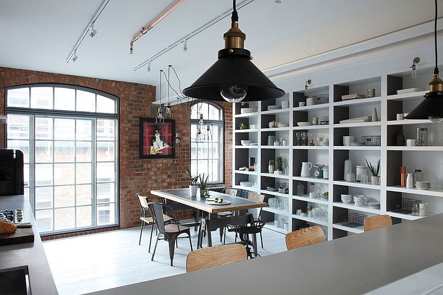 Kitchen and dining room of the industrial London home with a brick wall