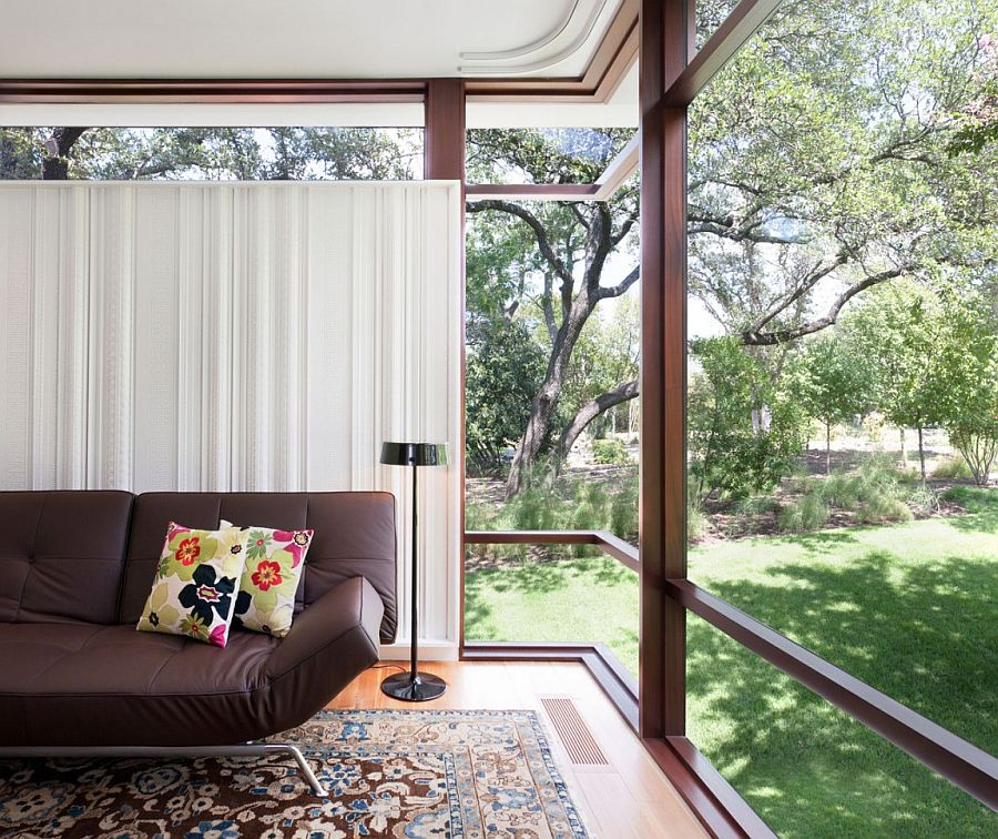 Large glass windows open up the sitting area to the lush green landscape outside