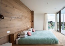 Lovely bedroom with bedside pendant lights and wooden headboard wall