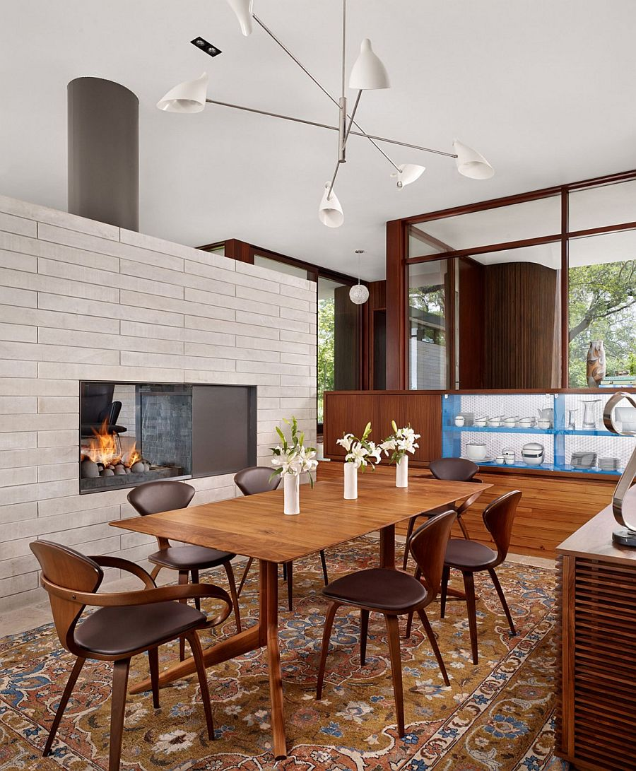 Modern dining room with fireplace and large glass walls
