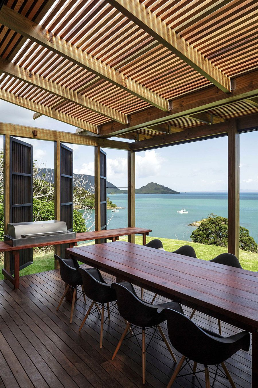 Outdoor dining space under pergola with stunning sea views in New Zealand