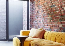 Plush-couch-in-bright-yellow-adds-color-to-the-creative-sitting-area-in-brick-glass-and-steel-217x155