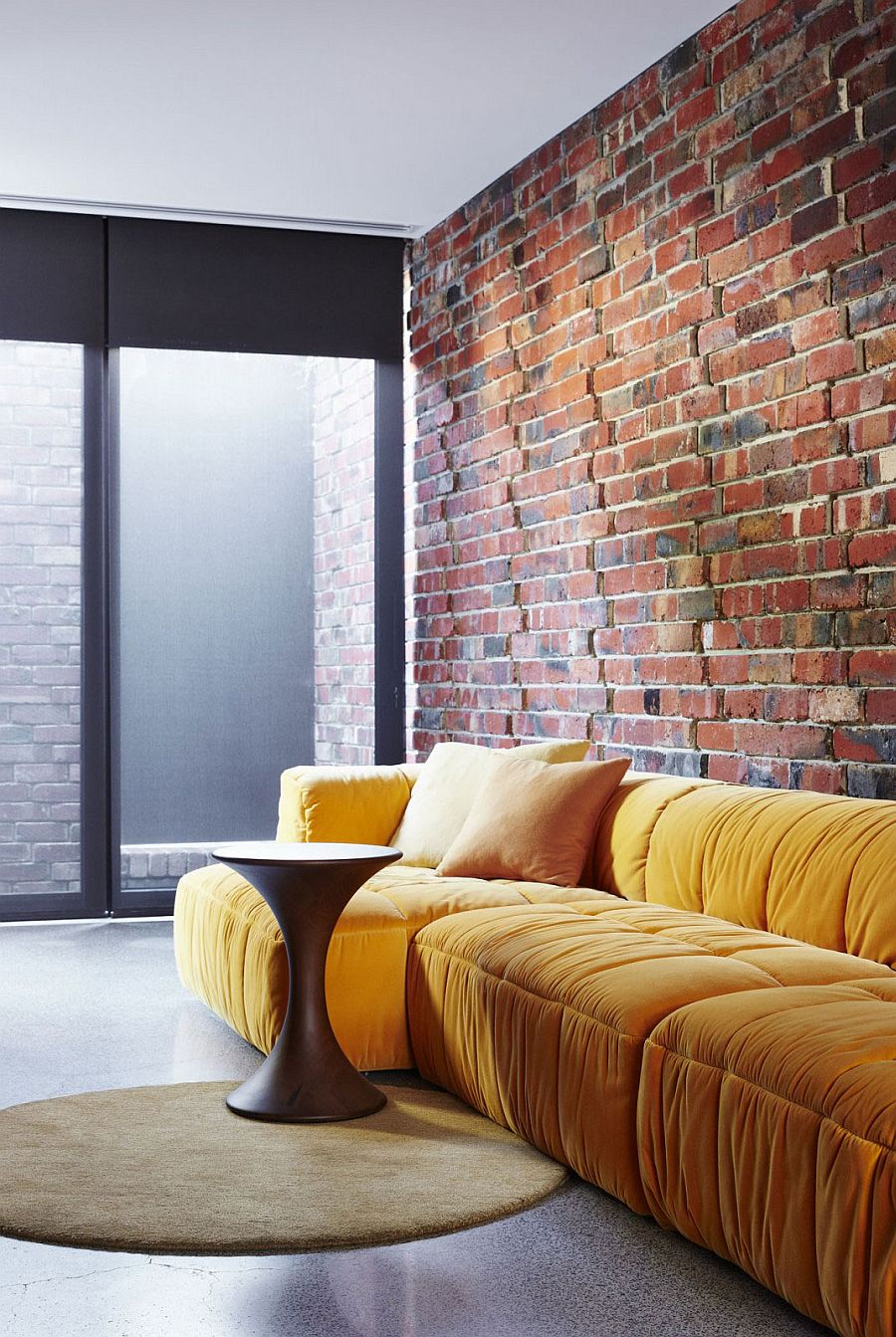 Plush couch in bright yellow adds color to the creative sitting area in brick, glass and steel