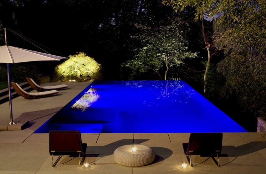 Relaxing backyard with LED pool lighting and an illuminated tree
