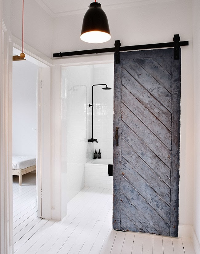 Reused old barn door creates a fabulous entrance for the Scandinavian bathroom [Design: MR.FRÄG]