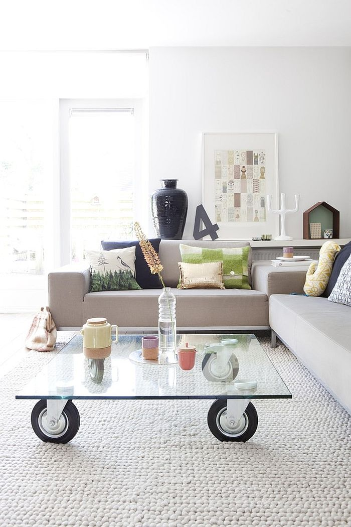 ... Scandinavian living room with glass coffee table on wheels [Design:  Gosto Design & Lifestyle