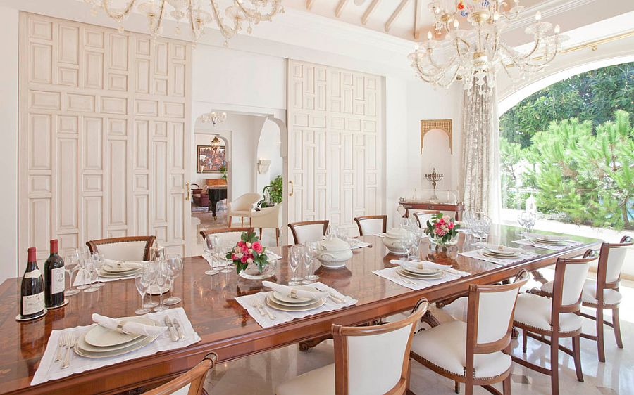 Sliding doors and glittering chandeliers transform the cool dining room [Design: Inson Dubois Wood]