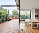 Sliding glass doors connect the new living area with the wooden deck outside