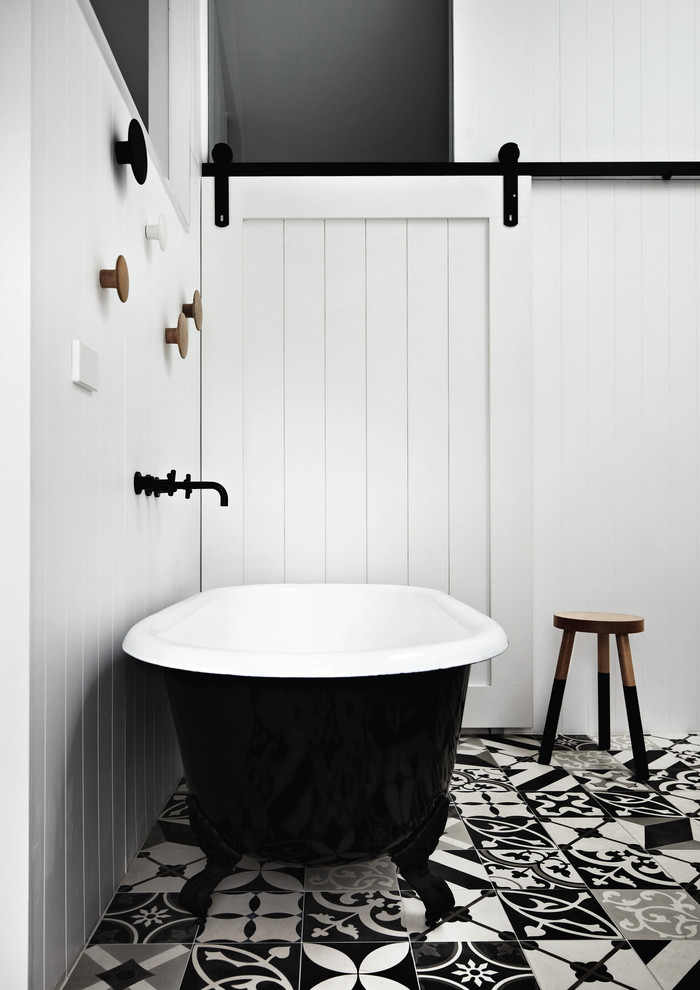 Small black and white bathroom with lovely flooring and barn door [Design: Whiting Architects]