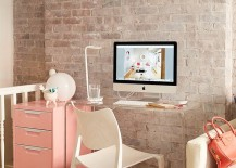 Small corner workspace with transparent desk and a pastel pink cabinet