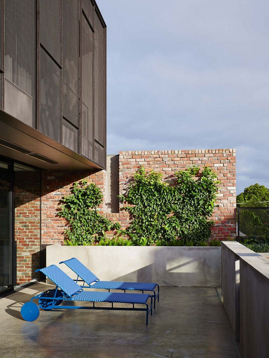 Small private porch of the melbourne how with a brick backdrop and colorful loungers