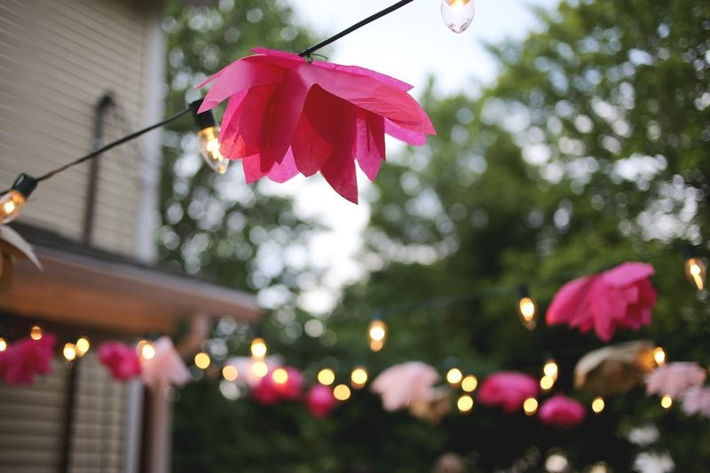 Tissue paper flowers embellish a string of outdoor lights