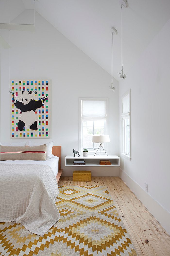 Wall art and chic rug add color and pattern to the stylish Scandinavian bedroom [Design: Texas Construction Company]