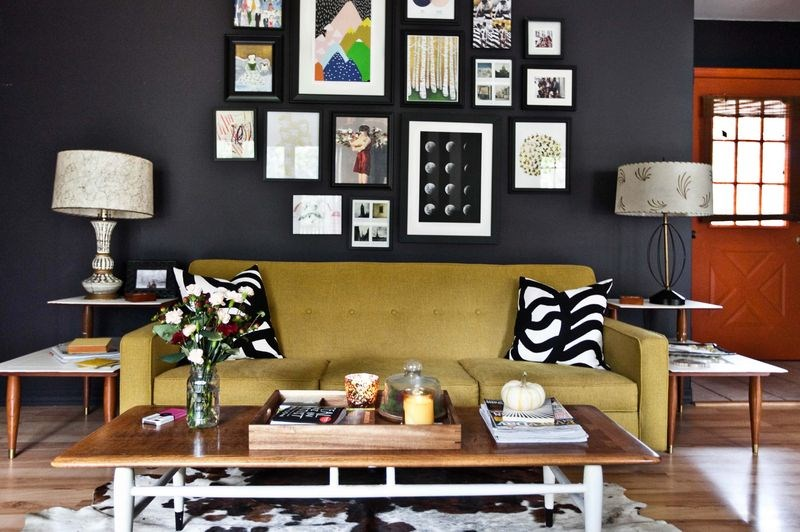 A gallery grouping of art pops against black walls decoist - Picture wall ideas for living room ...