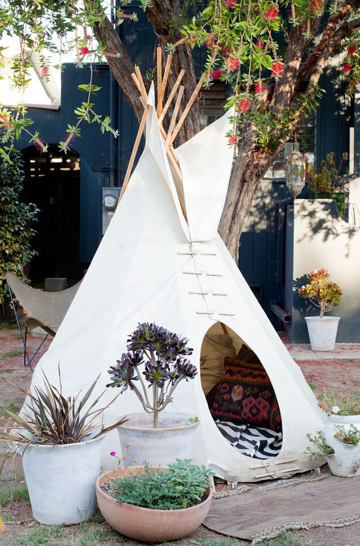 A trio of potted plants in front of a tipi