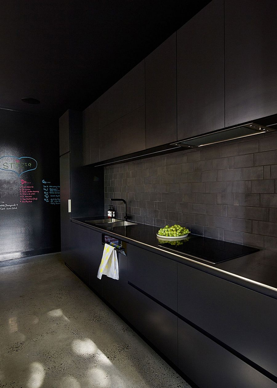 Black kitchen idea with tiled backsplash and a chalkboard wall