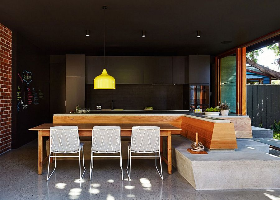 Dark kitchen backdrop lets the bright yellow pendant shine through