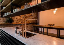 Exposed pipes accentuate the industrial flair of this custom kitchen [Design: OMG Projects]