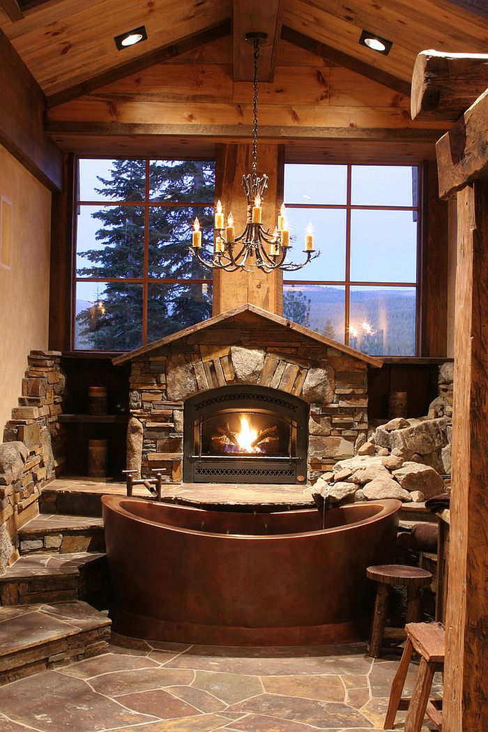 Fabulous cabin-style bathroom with copper bathtub, fireplace and large windows [Design: High Camp Home]