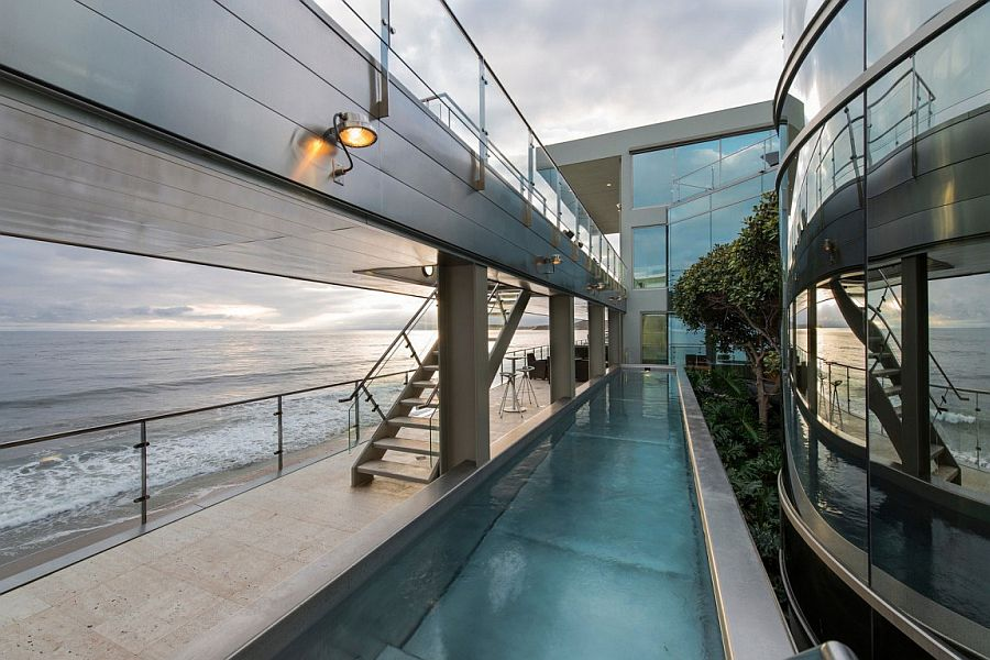 Lap pool and walk way along with an outdoor lounge next to the ocean