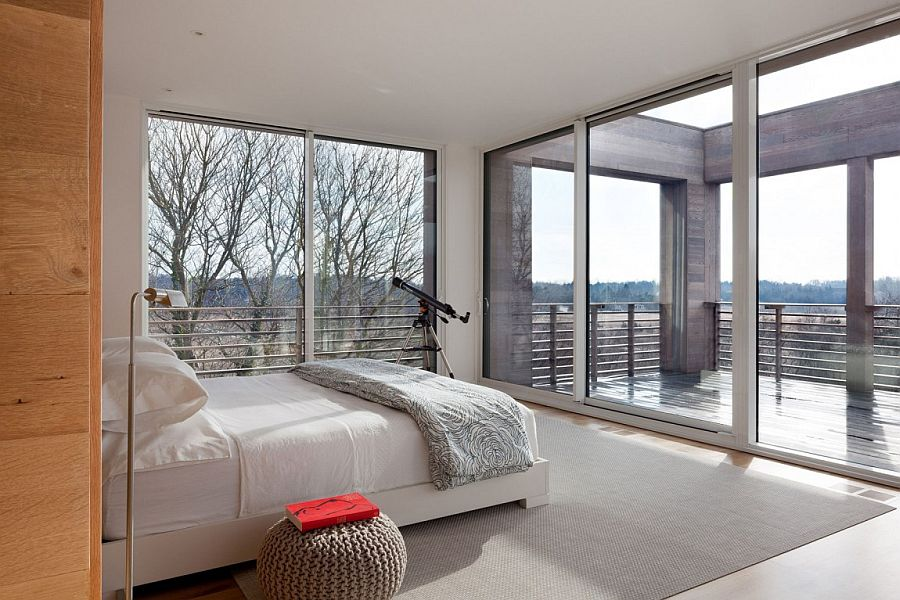 Large sliding doors and windows open the master bedroom towards the view outside