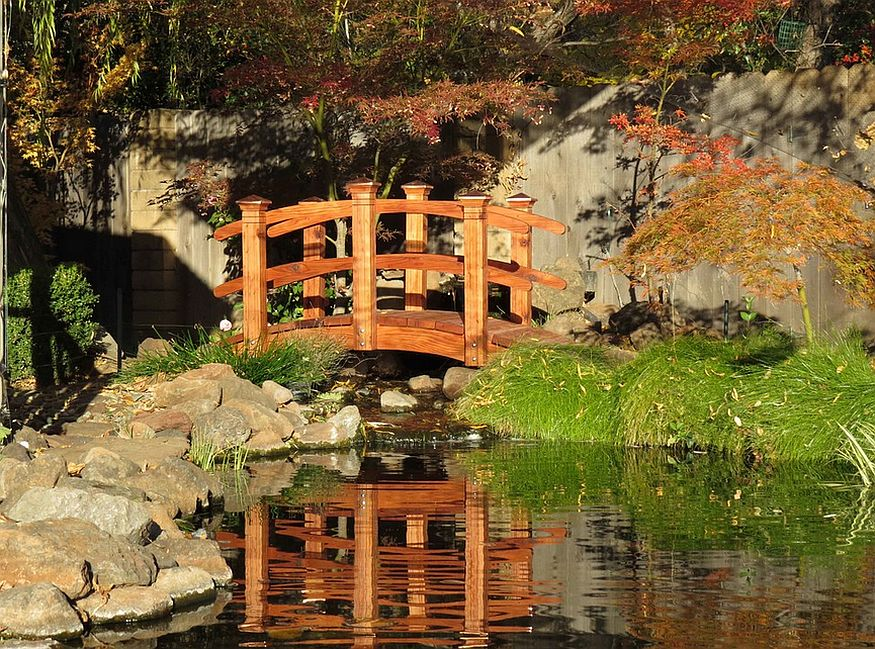 Mesmerizing water garden with an arched bridge in Oriental style [Design: Redwood Garden Bridges]