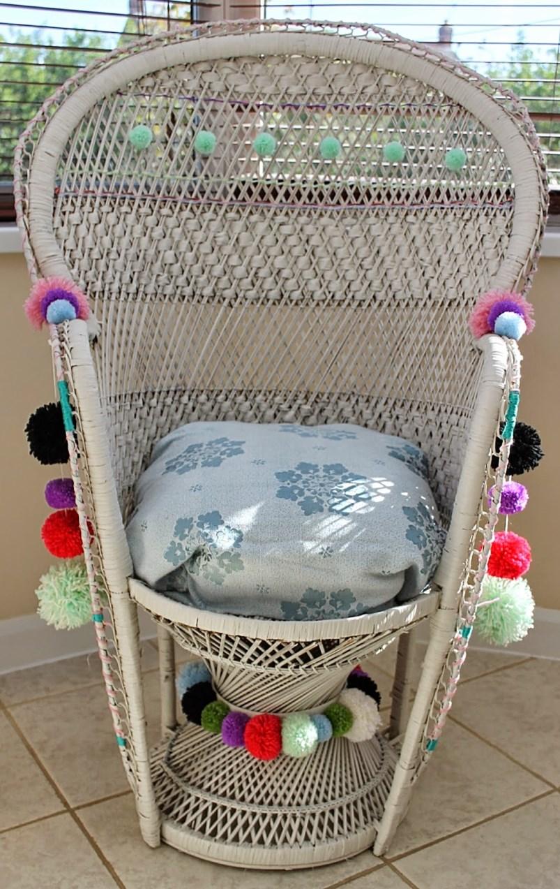 Pom poms adorn a woven peacock chair