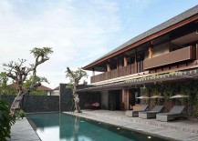 Pool area of the lavish private villa in Bali surrounded by natural greenery and wooden deck
