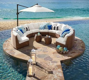 Pottery Barn honey wicker sectional on rounded platform next to ocean