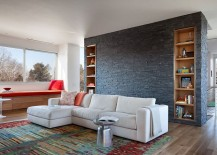 Slate wall with bookshelves acts as the accent addition in the chic Midcentury Modern living room