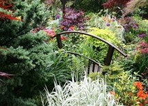Small garden bridge seems to be engulfed in colorful greenery [Design: Moffet Nursery & Garden Shop]