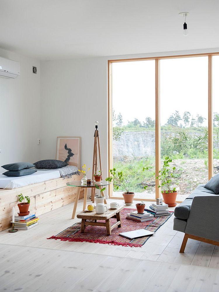 Tiny, informal living space with large glass window [From: Skälsö Arkitekter]