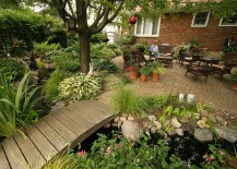 Small urban garden landscape with outdoor living, bridge and a water garden
