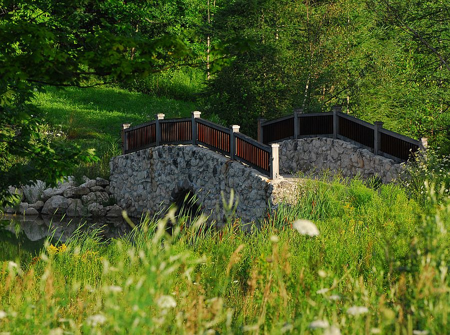 Stone bridge above a natural creek for the rustic retreat [Design: The Landmark Group]