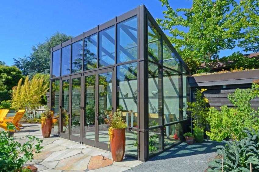 Stone patio near a modern greenhouse