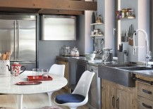 Stone sink and wooden cabinets along with the timeless Tulip chairs in the kitchen