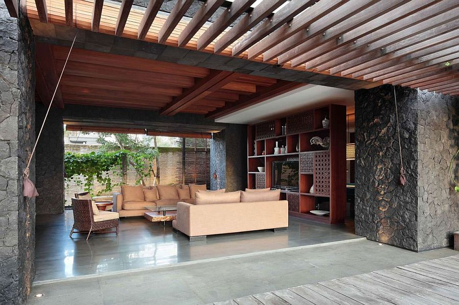 Stone walls shape the open living room of the Bali home